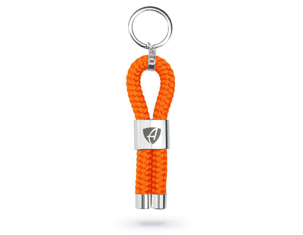 Vorderansicht eines orangenen CB Ammersee Schlüsselanhänger mit silberner Schelle und Gravur des Ammersee Logos der Modemarke AMMERSEE BAVARIA aus Bayern, Deutschland