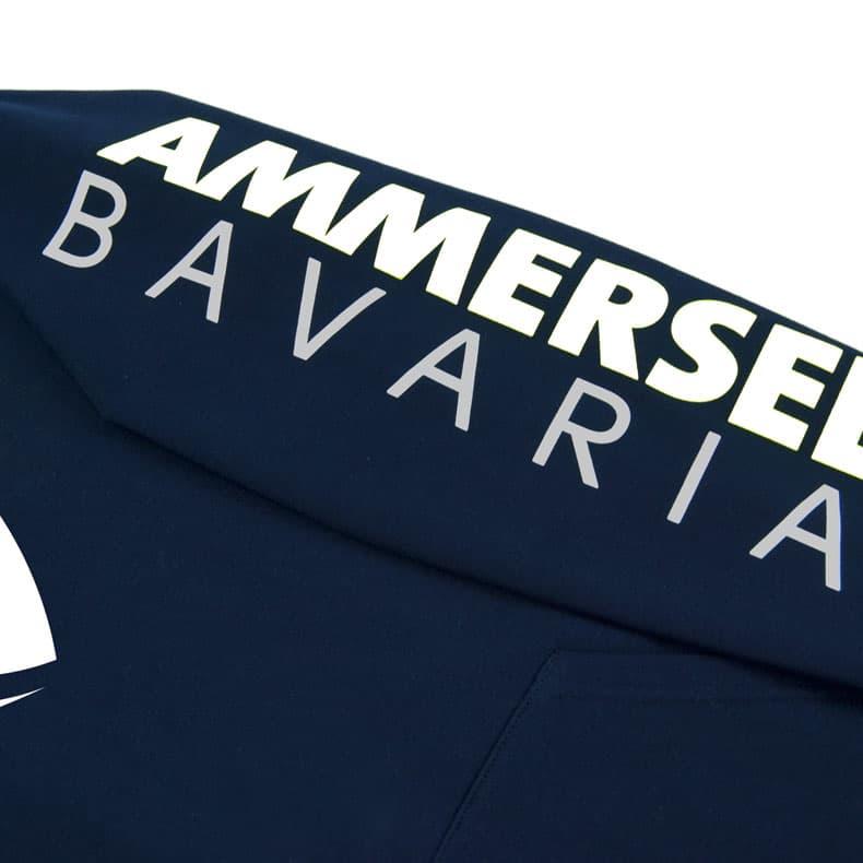 Detailaufnahme des linken Ärmel eines dunkelblauen Kapuzenpullover mit weiss-grauem Ammersee Design der Modemarke AMMERSEE BAVARIA aus Bayern, Deutschland