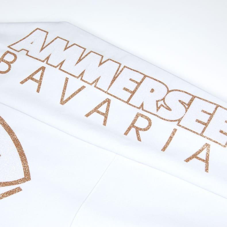 Detailaufnahme des linken Ärmel eines weissen Kapuzenpullover mit gold-weissem Glitzer Ammersee Design der Modemarke AMMERSEE BAVARIA aus Bayern, Deutschland