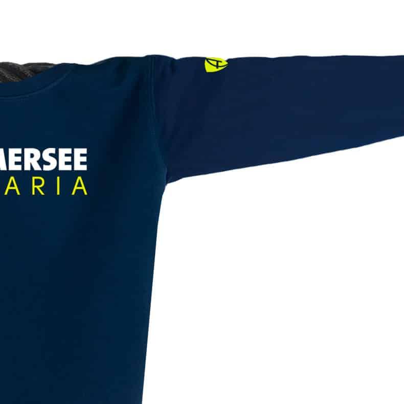 Ärmel eines dunkelblauen CT Pullover aus Bio-Baumwolle (Organic Bio Sweater) und recyceltem Polyester mit gelb-weissem Ammersee Design der Modemarke AMMERSEE BAVARIA aus Bayern, Deutschland
