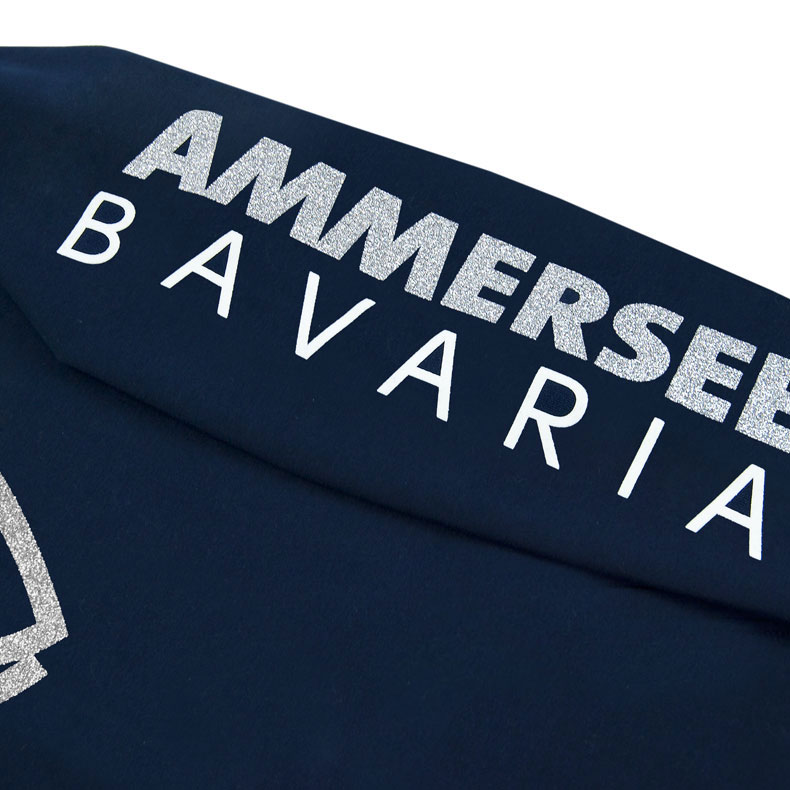 Detailaufnahme des linken Ärmel eines dunkelblauen Pullover mit weiss-silber-glitzerndem Ammersee Design der Modemarke AMMERSEE BAVARIA aus Bayern, Deutschland