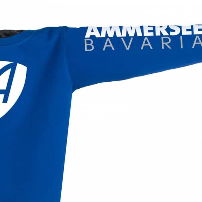 Ausschnitt Vorderansicht eines mittelblauen CB Pullover aus Bio-Baumwolle (Organic Bio Sweater) und recyceltem Polyester mit weiss-grauem Ammersee Design der Modemarke AMMERSEE BAVARIA aus Bayern, Deutschland