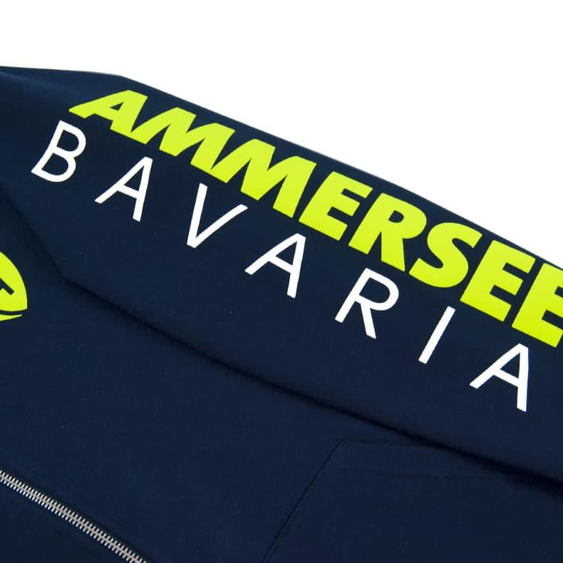 Detailaufnahme des linken Ärmel eines dunkelblauen Kapuzenjacke mit gelb-weissem Ammersee Design der Modemarke AMMERSEE BAVARIA aus Bayern, Deutschland