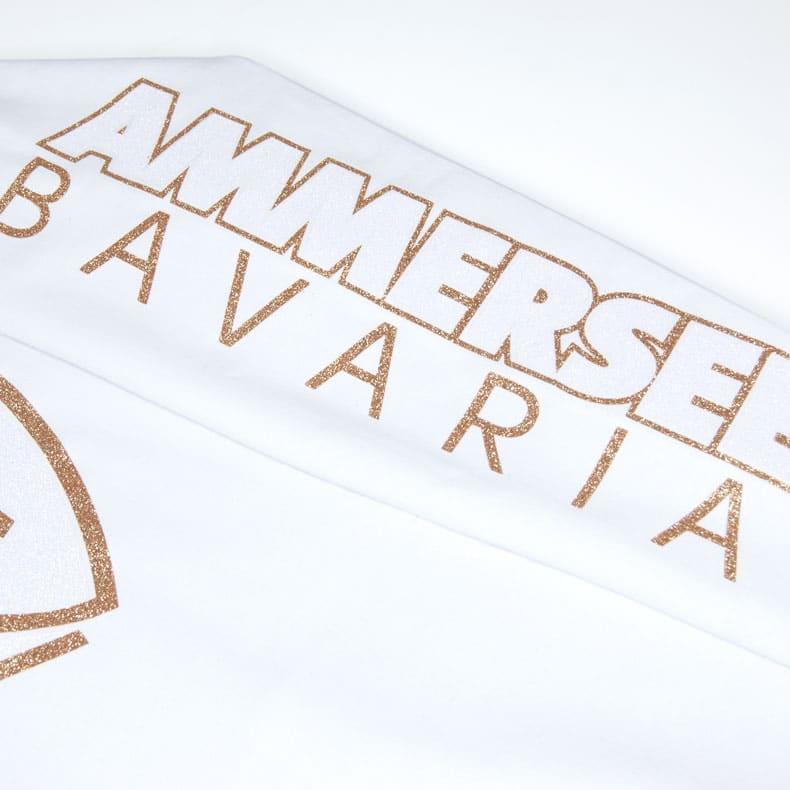 Detailaufnahme des linken Ärmel eines weissen Pullover mit weiss-gold-glitzerndem Ammersee Design der Modemarke AMMERSEE BAVARIA aus Bayern, Deutschland