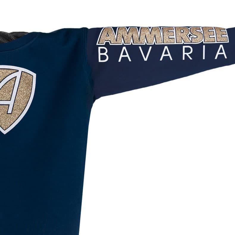 Ärmel eines dunkelblauen CBe Pullover aus Bio-Baumwolle (Organic Bio Hoodie) und recyceltem Polyester mit weiss-gold-glitzerndem Ammersee Design der Modemarke AMMERSEE BAVARIA aus Bayern, Deutschland