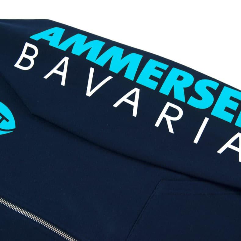 Detailaufnahme des linken Ärmel eines dunkelblauen Kapuzenjacke mit türkis-weissem Ammersee Design der Modemarke AMMERSEE BAVARIA aus Bayern, Deutschland