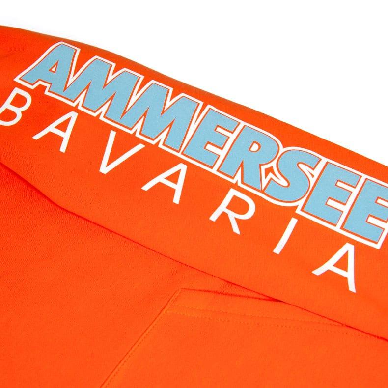 Detailaufnahme des linken Ärmel eines orangenen CBo Kapuzenpullover mit weiss-hellblauen Ammersee Design der Modemarke AMMERSEE BAVARIA aus Bayern, Deutschland