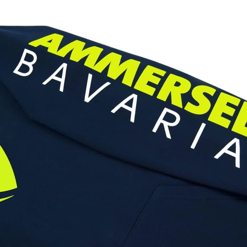 Detailaufnahme des linken Ärmel eines dunkelblauen Kinder Kapuzenpullover mit weiss-lime-gelben Ammersee Design der Modemarke AMMERSEE BAVARIA aus Bayern, Deutschland