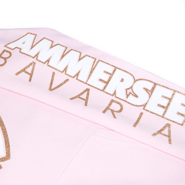 Detailaufnahme des linken Ärmel eines rosernen CBo Kinder Kapuzenpullover mit weiss-gold-glitzerndem Ammersee Design der Modemarke AMMERSEE BAVARIA aus Bayern, Deutschland