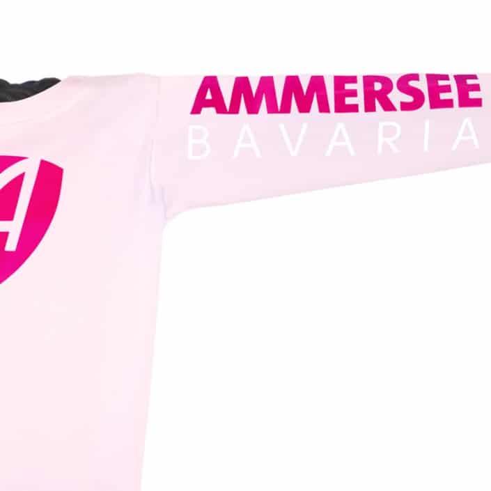 Ausschnitt Vorderansicht eines hellrosa CB Kinder Longsleeve aus Bio-Baumwolle (Organic Bio T-Shirt) mit magenta-weissem Ammersee Design der Modemarke AMMERSEE BAVARIA aus Bayern, Deutschland