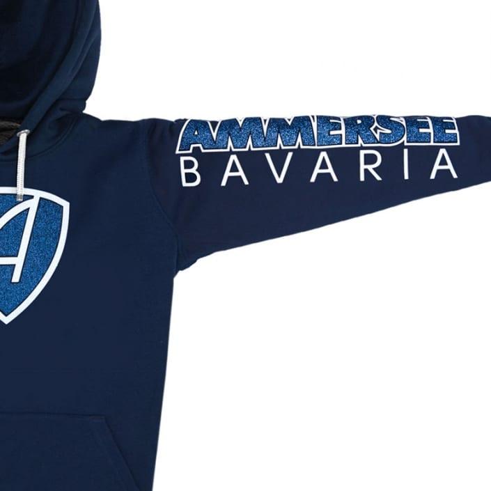 Ausschnitt Vorderansicht eines dunkelblauen CBo Kapuzenpullover aus Bio-Baumwolle (Organic Bio Hoodie) und recyceltem Polyester mit weiss-blau-glitzerndem Ammersee Design der Modemarke AMMERSEE BAVARIA aus Bayern, Deutschland