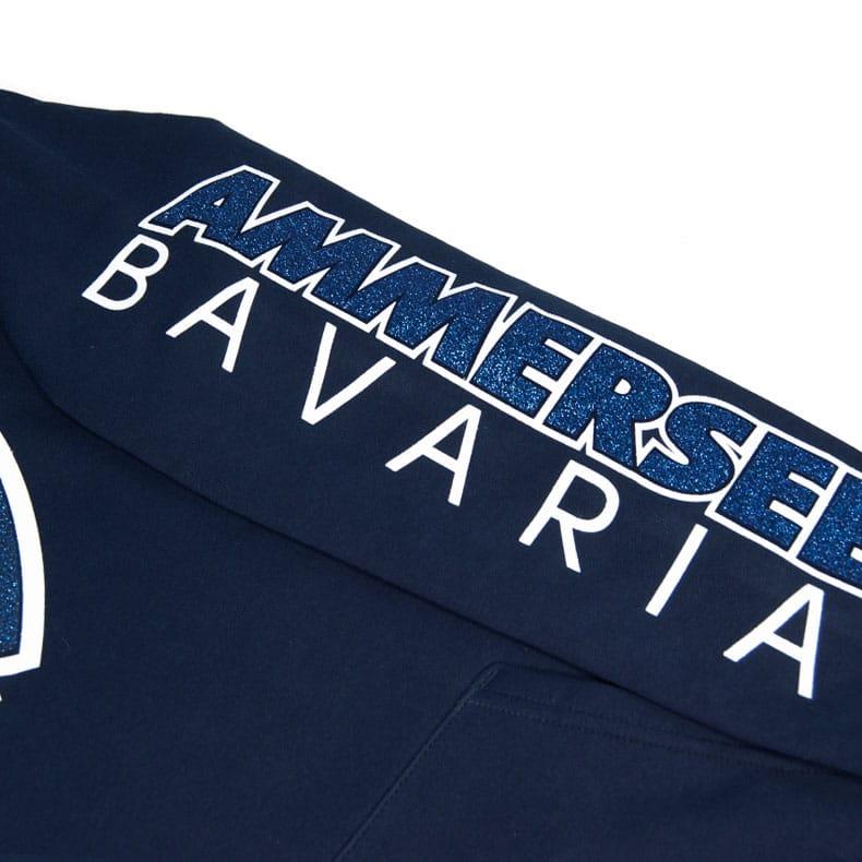 Detailaufnahme des linken Ärmel eines dunkelblauen Cbo Kapuzenpullover mit weiss-blau-glitzerndem Ammersee Design der Modemarke AMMERSEE BAVARIA aus Bayern, Deutschland