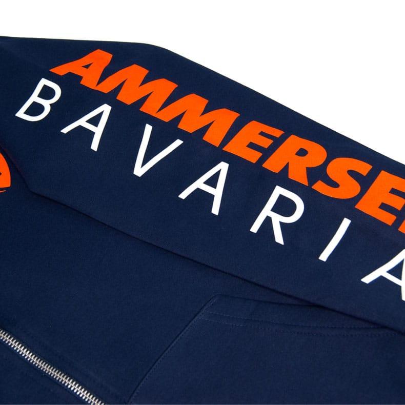 Detailaufnahme des linken Ärmel eines dunkelblauen Kapuzenjacke mit orange-weissem Ammersee Design der Modemarke AMMERSEE BAVARIA aus Bayern, Deutschland