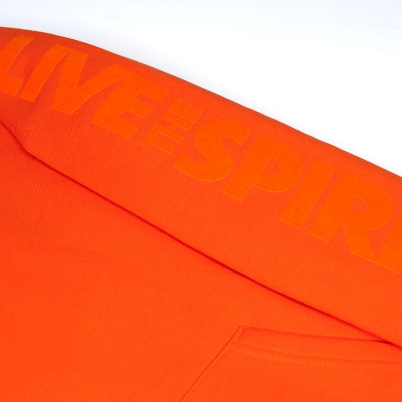 Detailaufnahme des linken Ärmel eines orangenen SB Kapuzenpullover mit orangenem Ammersee Design der Modemarke AMMERSEE BAVARIA aus Bayern, Deutschland